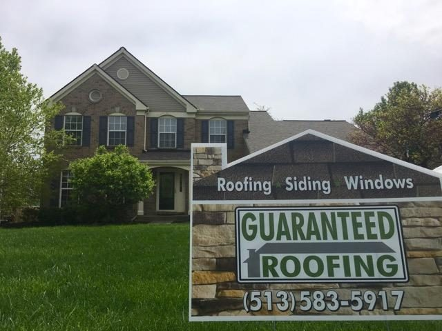 Guaranteed Roofing sign in front of house