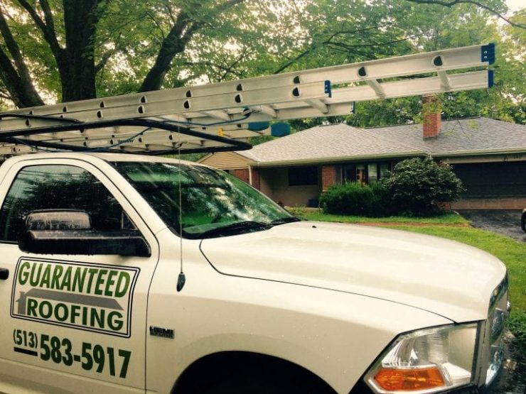 Guaranteed Roofing truck in front of home