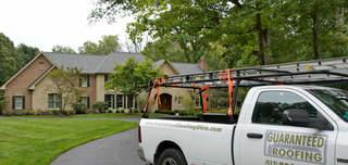 Guaranteed Roofing truck in front of house